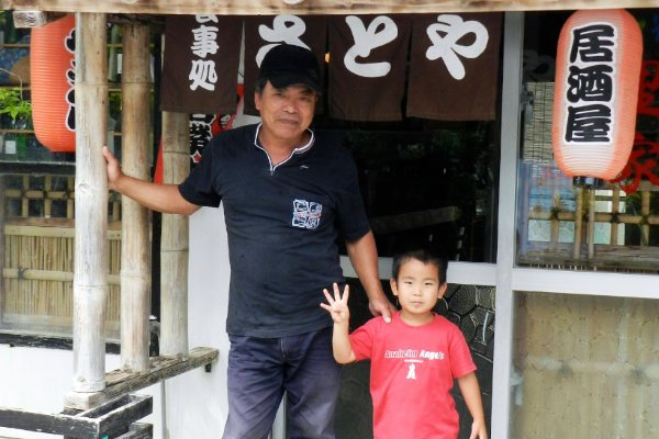 A photo of Maehama-san and his grandson in front of the inn's restaurant