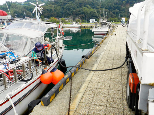 A photo of a man serving fuel from the fuel track to a yacht in fishing port